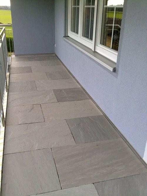 Balkon aus grauem Sandstein mit spaltrauer Oberfläche