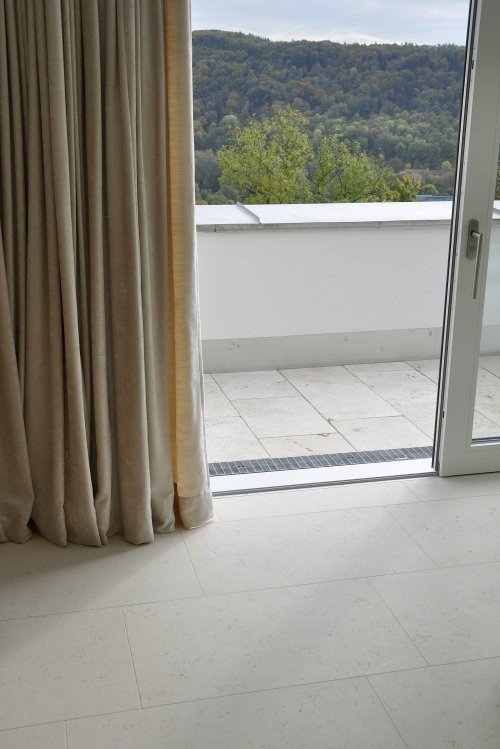 Ausblick vom Wohnbereich auf Terrasse aus hellem Naturstein